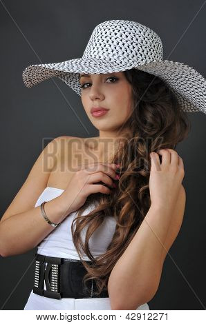 Beautiful young brunette girl posing pretty to camera in the studio wearing white dress and hat