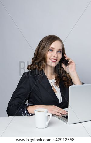 Pretty business woman at office desk.