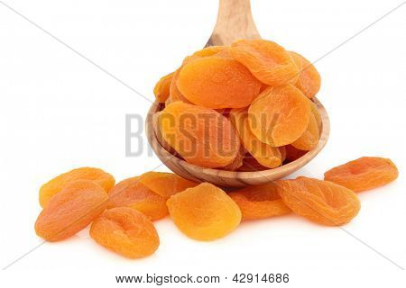 Dried apricot fruit in an olive wood spoon over white background.