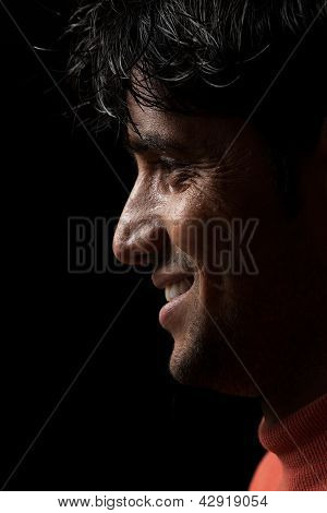 Portrait of young Indian man smiling over dark