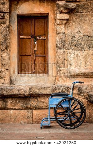 wheelchair on a background of a stone wall