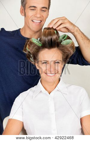 Portrait of mid adult female client with hairstylist rolling her hair
