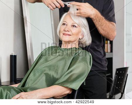 Senior woman having hair cut at beauty salon