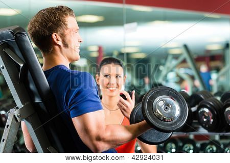 Man or Bodybuilder with his personal fitness trainer in the gym exercising sport with dumbbells, closeup