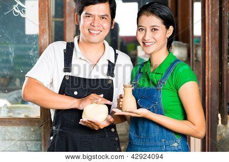 Zwei Asiaten oder Indonesier halten stolz gebacken, Ton und eine fertige handgemachte vase