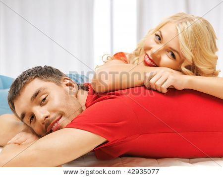 bright picture of happy couple lying at home (focus on man)