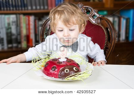 Little Boy Celebrating Third Birthday And Blowing Off  Candles