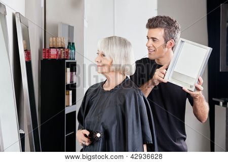 Happy male hairstylist showing finished haircut to senior woman at salon