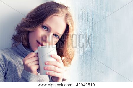 Beautiful Dreamy Young Woman With A Cup Of Hot Coffee At The Window In The Rain