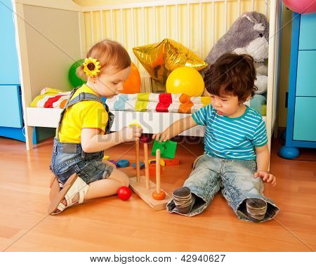 Boy And Girl Playing With Toy Pyramid Puzzle