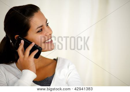 Young Woman Speaking On Cellphone Looking Left