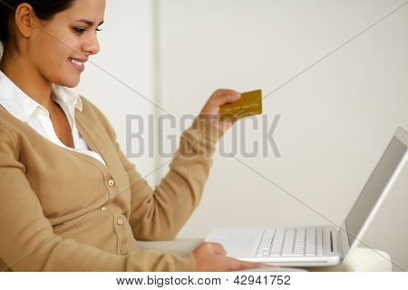 Young Woman Holding A Gold Credit Card With Laptop