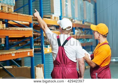 warehouse workers men inspecting and checking rack arrangement of furniture laminate flooring