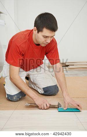 carpenter worker installing wood parquet board during flooring work with hammer