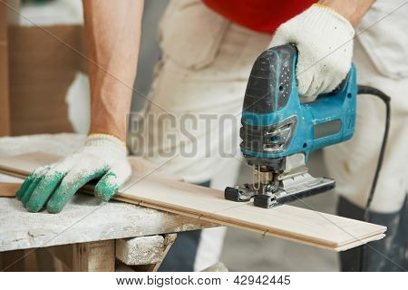 Close-up process of cutting parquet floor board with jigsaw