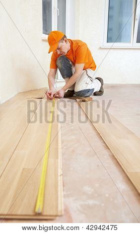 parquet floor layer carpenter worker installing wood parquet board during flooring work