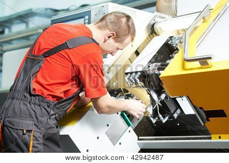 mechanical worker of cnc grinding cutting machine at tool workshop manufacturing