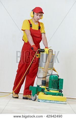 carpenter doing parquet Wood Floor polishing maintenance work by grinding machine