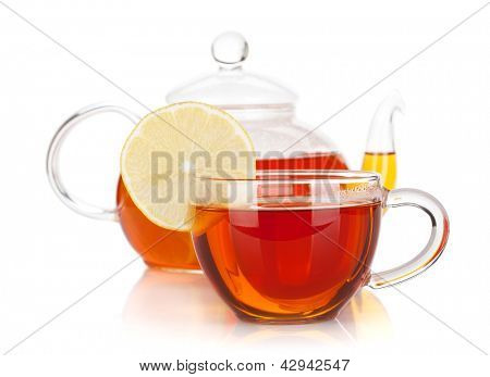 Glass cup with lemon slice and teapot of black tea. Isolated on white background
