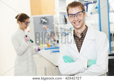 Portrait of young smiling male researcher in front of female researcher carrying out scientific test in chemistry laboratory