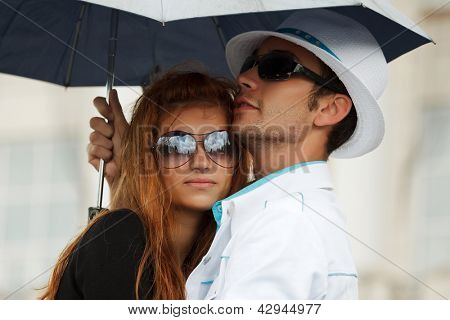 Young couple with umbrella in the rain