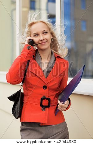 Young businesswoman with a folder calling on the phone