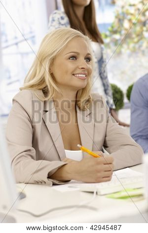 Portrait of attractive young businesswoman sitting at desk, writing notes, smiling.