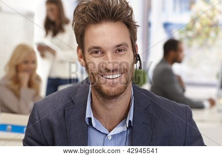 Closeup portrait of handsome male customer service representative smiling happy.