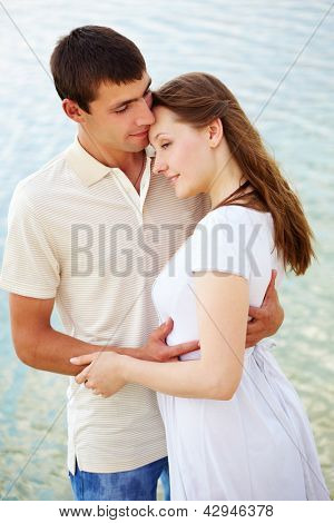 Photo of peaceful couple enjoying being together with blue water on background