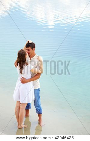 Photo of amorous couple standing in water enjoying summer vacation