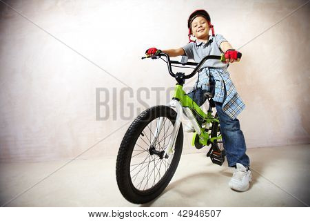 Portrait of happy boy on bicycle looking at camera