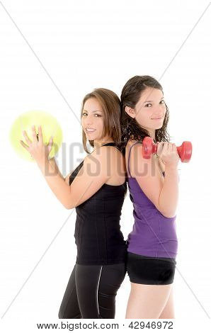 Two women doing exercises with barbell  and ball