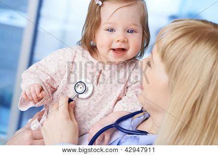 Cute baby being examined by female doctor in hospital