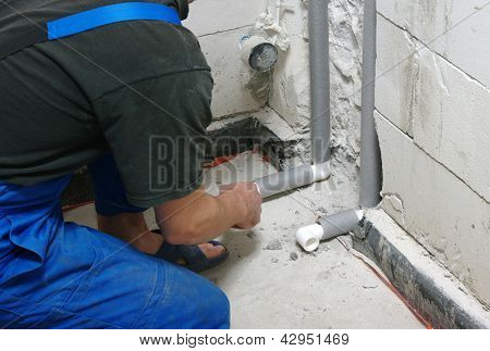 Plumber installing pipes in home