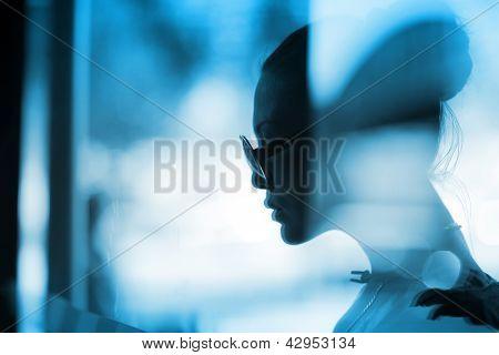 Beautiful fashion profile portrait of woman behind glass. Closeup, shallow DOF.