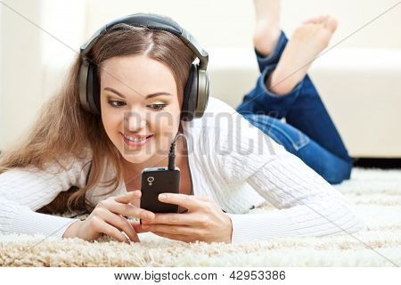 woman lying on carpet and listening to music