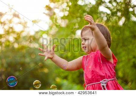 little girl at park with bubbles