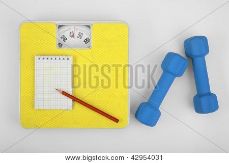 Scales, notebook with pencil and a dumbbell.