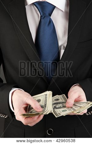Business man counts money close-up