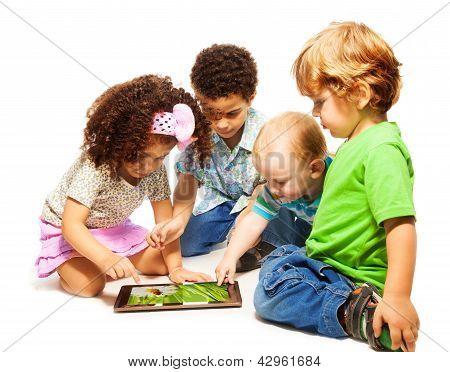 Quatro crianças pouco jogando em comprimidos