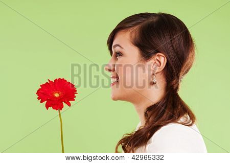 Pretty woman holding red flower on green background