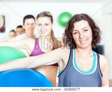 Group of people holding pilates ball at the gym
