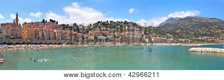 MENTON - JULY 07: Panorama of small town of Menton with red houses along public beach on hot summer day. The town is very popular holiday resort on French Riviera in Menton, France on July 07, 2012.