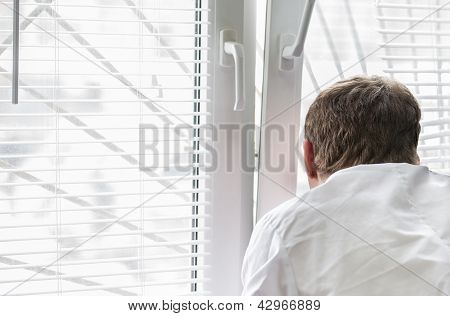 Man Looks Out The Window