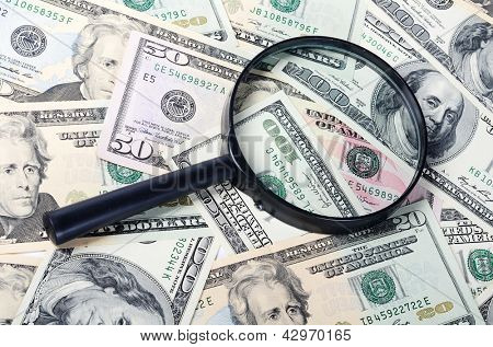 The magnifying glass lying on banknotes close-up