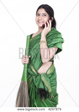 Female Talking On Her Cell Phone While Sweeping