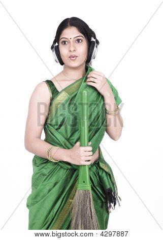 Schöne junge asiatische Frau indischen Ursprungs halten einen Besen und Gesang
