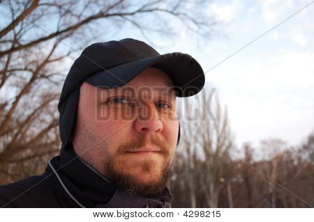 Portrait Of Young Man With Cap On Head. Outdoors.
