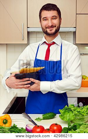 smiley handsome man in blue apron holding pan with spaghetti