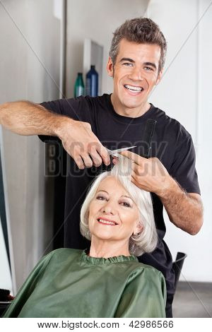 Portrait of happy hairdresser cutting female client's hair at salon
